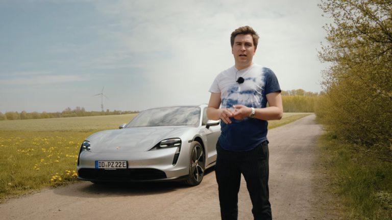 Mann steht vor grauem Porsche Taycan mit Feld und Windrad im Hintergrund