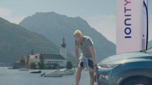 Mann schließt blauen Hyundai Kona electric an öffentlichen CCS-Lader an mit See und Bergen im Hintergrund