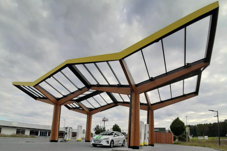 Hyundai IONIQ elektro mit XADER-Werbefolierung steht an einem überdachten öffentlichen Ladepunkt
