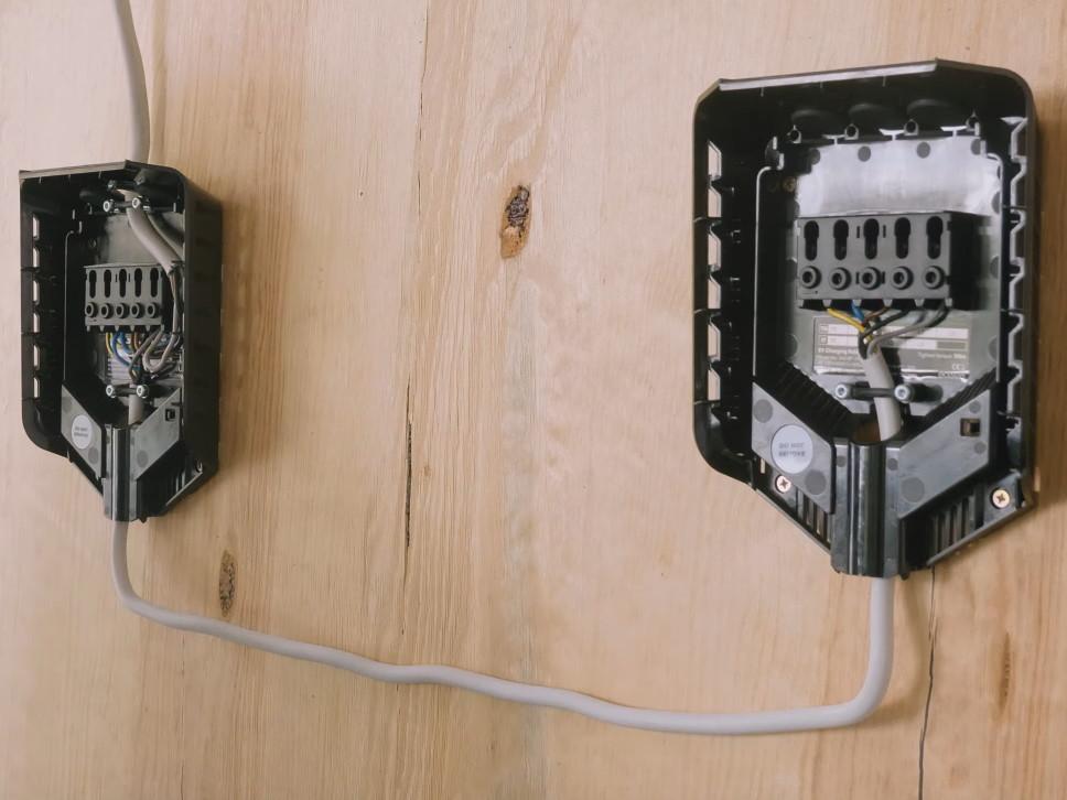 Zwei Backplates von Easee Home Wallboxen sind über ein Stromkabel miteinander verbunden